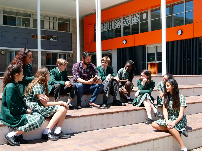 Outside classroom discussion with teacher and a group of students